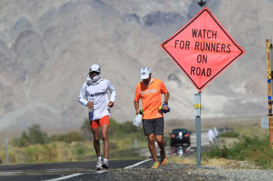 Ray Sanchez (L) of Sacramento, California runs along highway 136 north of Lake Owens as he approaches the town of Lone Pine during the AdventureCORPS Badwater 135 ultra-marathon race on July 16, 2013 outside of Death Valley National Park, California.