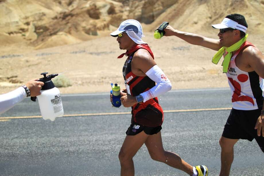 Oswaldo Lopez of Madera, California is cooled by his crew as he runs in the AdventureCORPS Badwater 135 ultra-marathon race on July 15, 2013 in Death Valley National Park, California.