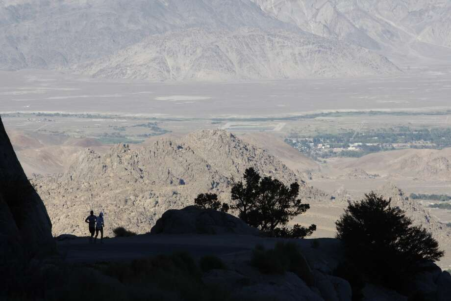 The Alabama Hills and the town of Lone Pine are seen in the distance as runners ascent Whitney Portal Road to the finish of the AdventureCORPS Badwater 135 ultra-marathon race on July 16, 2013 outside of Death Valley National Park, California.