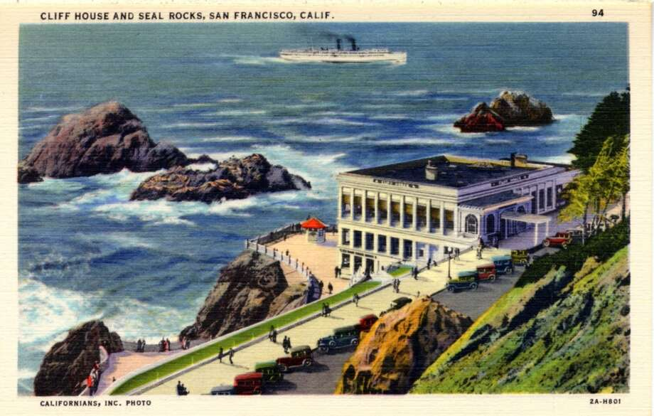 A vintage linen postcard showing a 1932 bird's eye view of the Cliff House and Seal Rock. Automobiles line the parking areas and pedestrians walk on a sidewalk along the shore.