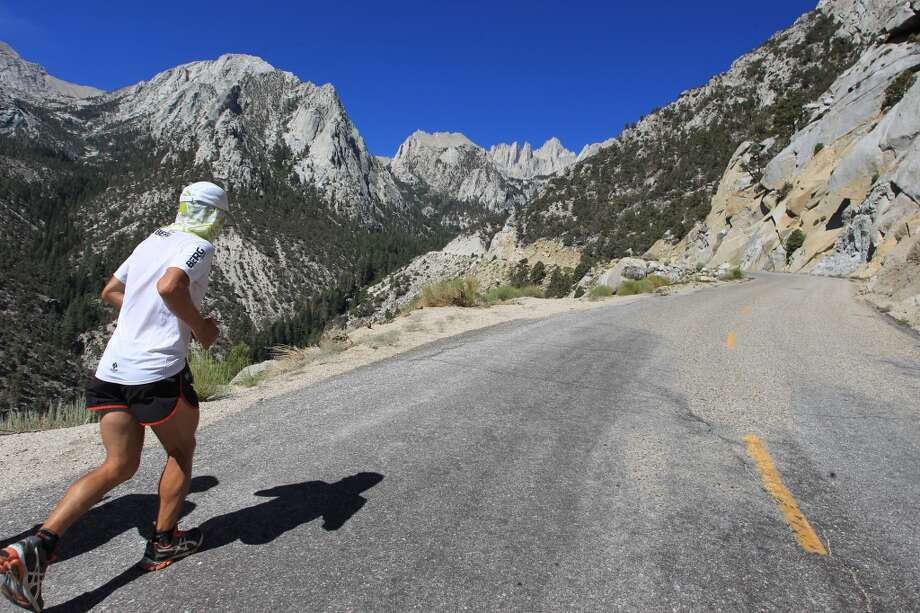 The tallest U.S. peak outside of Alaska, 14,495-foot Mount Whitney, is seen in the far distance as Carlos Alberto Gomas De Sa from Portugal, a first-time competitor in the event, runs up Whitney Portal Road on his way to win the AdventureCORPS Badwater 135 ultra-marathon race on July 16, 2013 outside of Death Valley National Park, Calif.