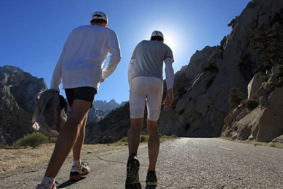 Jay Smithberger of Granville, Ohio (R) walks toward Mount Whitney, seen in the distance, during the ascent of Whitney Portal Road to the finish of the AdventureCORPS Badwater 135 ultra-marathon race on July 16, 2013 outside of Death Valley National Park, California. Photo: David McNew, Getty Images / 2013 Getty Images