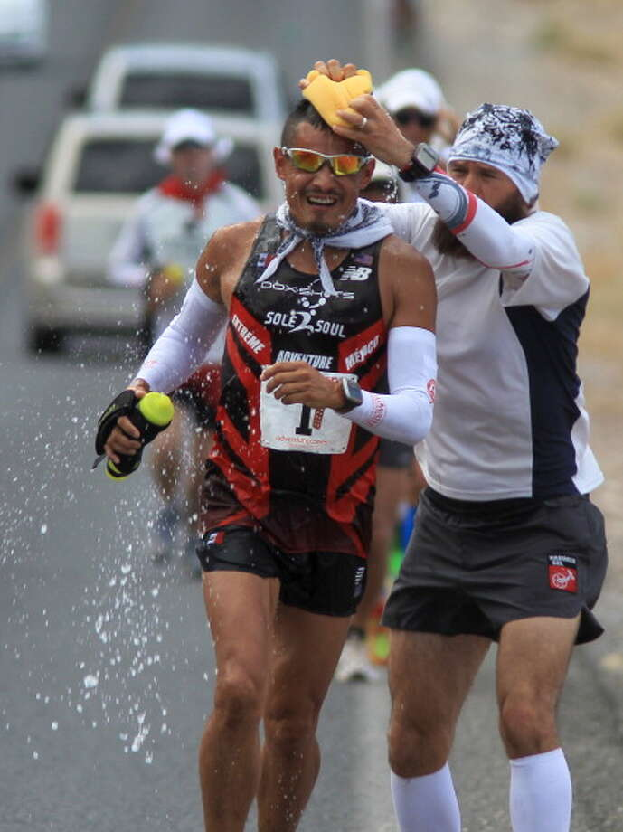 Oswaldo Lopez of Madera, California, who went on to win third place, is cooled during the AdventureCORPS Badwater 135 ultra-marathon race on July 15, 2013 in Death Valley National Park, California. Photo: David McNew, Getty Images / 2013 Getty Images