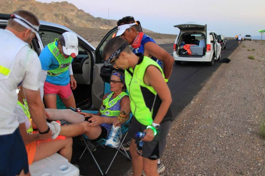 Lisa Smith-Blatchen of Driggs, Idaho receives first aid foot maintenance at Panamint Pass as night nears during the AdventureCORPS Badwater 135 ultra-marathon race on July 15, 2013 in Death Valley National Park, California.