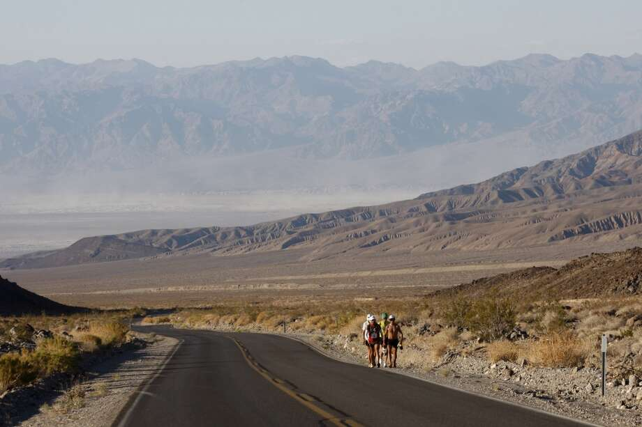 Oswaldo Lopez of Madera, California, Carlos Alberto of Portugal and support crew members climb the grade toward Townes Pass during the AdventurCORPS Badwater 135 ultra-marathon race on July 15, 2013 in Death Valley National Park, California.