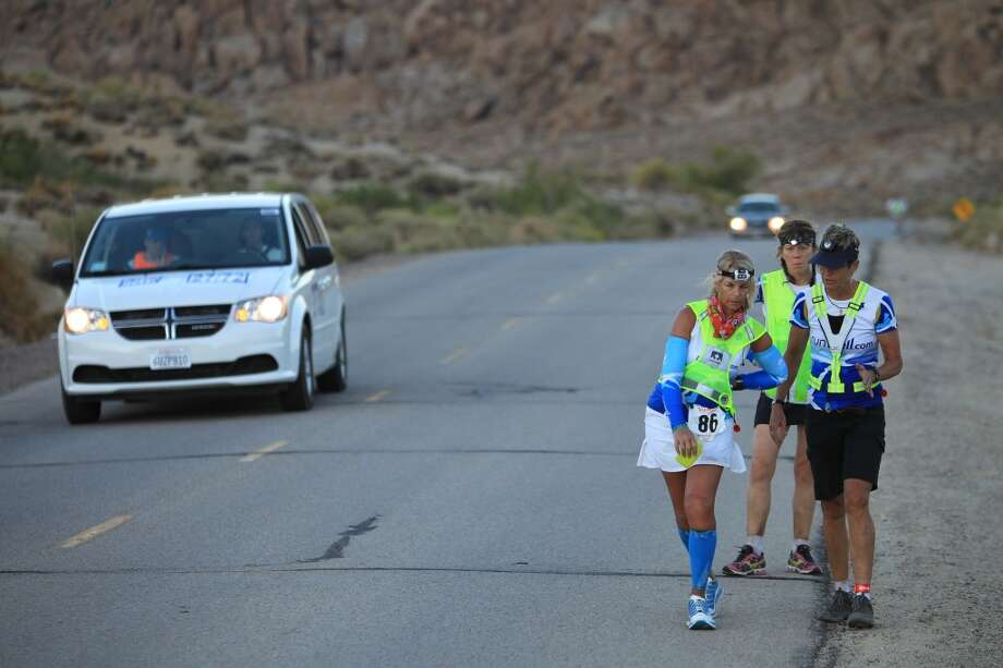 Linda Quirk of Jacksonville, Florida is bent over in back pain, a common condition among the athletes in the event after running 100 miles, as she makes the final ascent up Whitney Portal Road to the finish of the AdventureCORPS Badwater 135 ultra-marathon race on July 16, 2013 outside of Death Valley National Park, California.