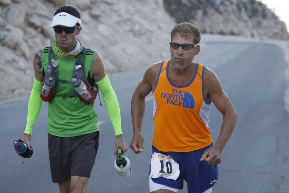 Dean Karnazes of Ross, California runs stiff with pain as he ascends the last few miles of Whitney Portal Road to the finish of the AdventureCORPS Badwater 135 ultra-marathon race on July 16, 2013 outside of Death Valley National Park, California.