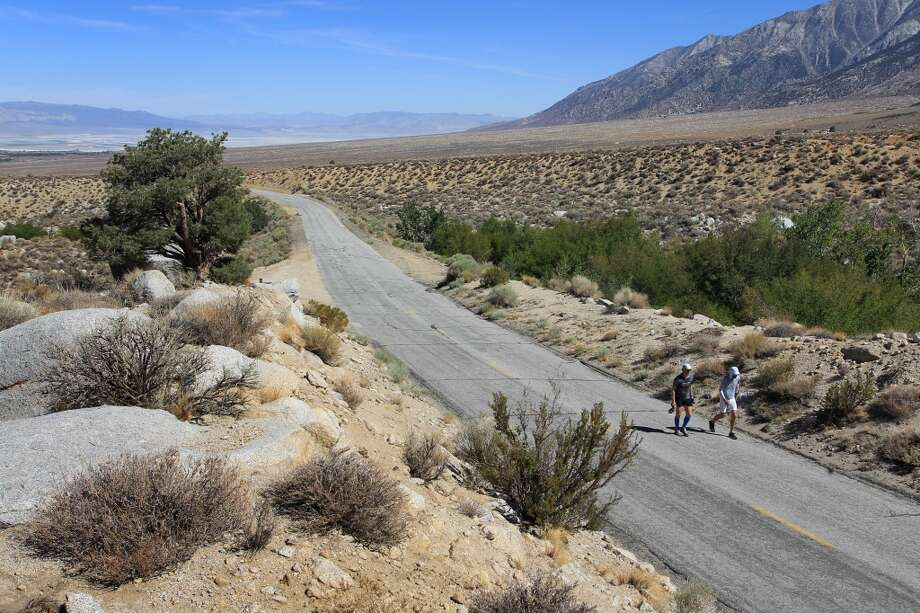 Jay Smithberger (R) of Granville, Ohio ascends Whitney Portal Road toward the finish of the AdventureCORPS Badwater 135 ultra-marathon race on July 16, 2013 outside of Death Valley National Park, California.
