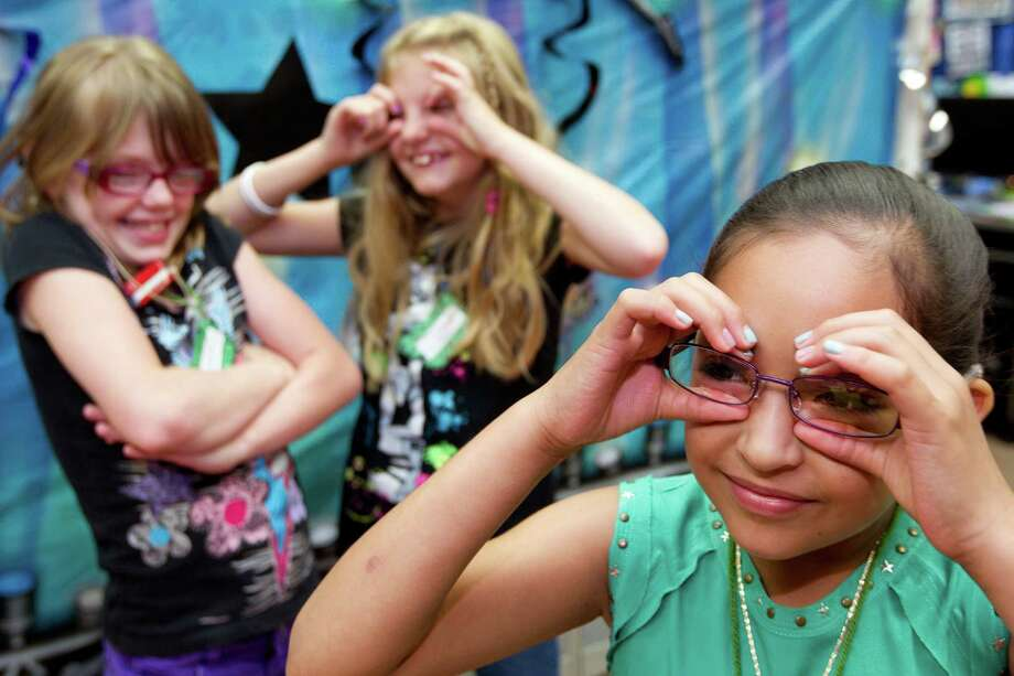 "Jackeline Medina, 8, right, and campmates, Alexandria Easton, 10, left, and Amanda Jacobs, 9, center, use their ""binoculars"" to search for clues during a learning exercise on bugs during the Project T.A.L.K. summer camp for children with hearing loss at The Center for Hearing and Speech Thursday, July 18, 2013, in Houston. Photo: Johnny Hanson, Houston Chronicle / © 2013  Houston Chronicle"