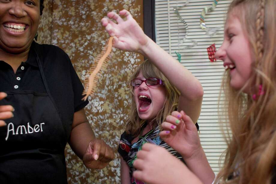 Learning about bugs, Alexandria Easton, 10, center, reacts when she picks up a plastic centipede next to campmate, Amanda Jacobs, 9, and Amber Webb, a University of Houston graduate student in speech communications, during a learning exercise at the Project T.A.L.K. summer camp for children with hearing loss at The Center for Hearing and Speech Thursday, July 18, 2013, in Houston. Photo: Johnny Hanson, Houston Chronicle / © 2013  Houston Chronicle