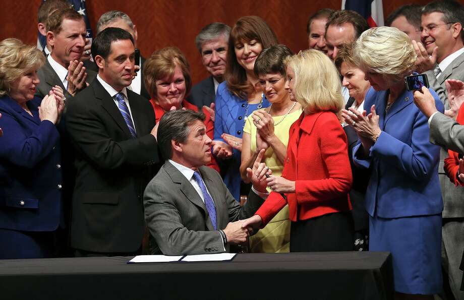 Gov. Rick Perry congratulates state Rep. Jodie Laubenberg, R-Parker, Thursday after signing into law the abortion-restrictions bill she helped sponsor.  Texas now has some of the strictest abortion laws in the nation. Photo: TOM REEL