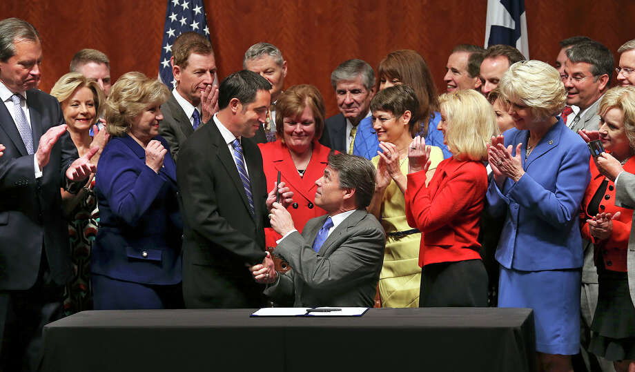 State Sen. Glenn Hegar R-Katy, gets a pen after Governor Rick Perry signs into law the abortions restrictions bill  on July 18, 2013. Photo: Tom Reel, San Antonio Express-News