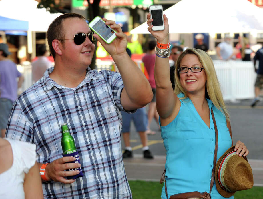 Charles Goodwin and Sarah Gavish wave their phones in the air as The Dirty Gems perform during Alive@Five at Columbus Park in Stamford on Thursday, July 18, 2013. Hearst Connecticut Newspapers are a sponsor of the event. Photo: Jason Rearick / Stamford Advocate