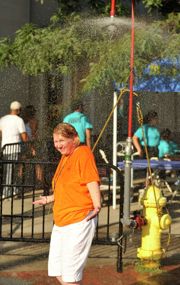 Event volunteer Donna Librandi cools off under a shower installed by the fire department during Alive@Five at Columbus Park in Stamford on Thursday, July 18, 2013. Hearst Connecticut Newspapers are a sponsor of the event. Photo: Jason Rearick / Stamford Advocate