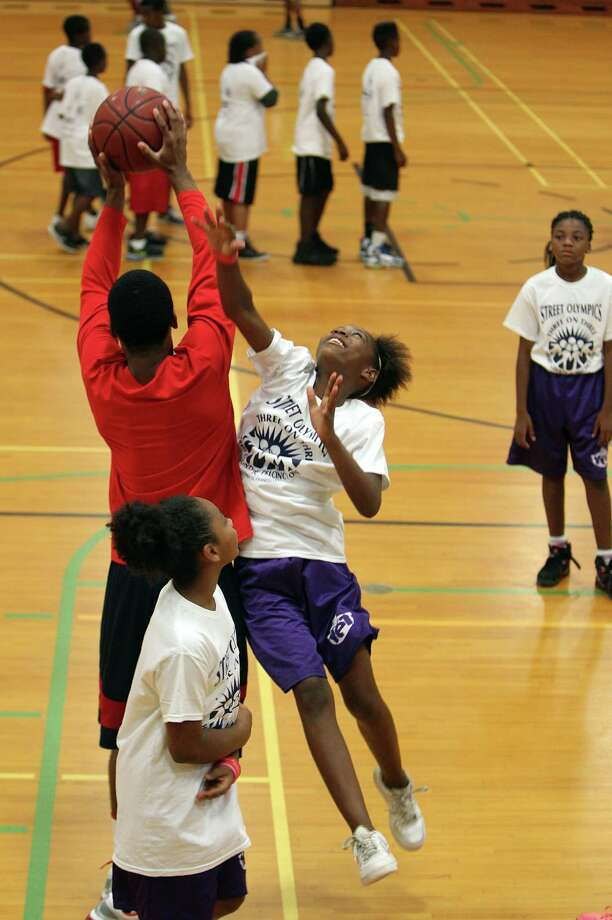 Andrea Green, 12, attempts to block University of Houston's basketball point guard Jimmie Jones during a warm up of the Harris County Street Olympics Three On Three Tournament at Fonde Recreation Center on Thursday, July 18, 2013, in Houston. Photo: Mayra Beltran / © 2013 Houston Chronicle