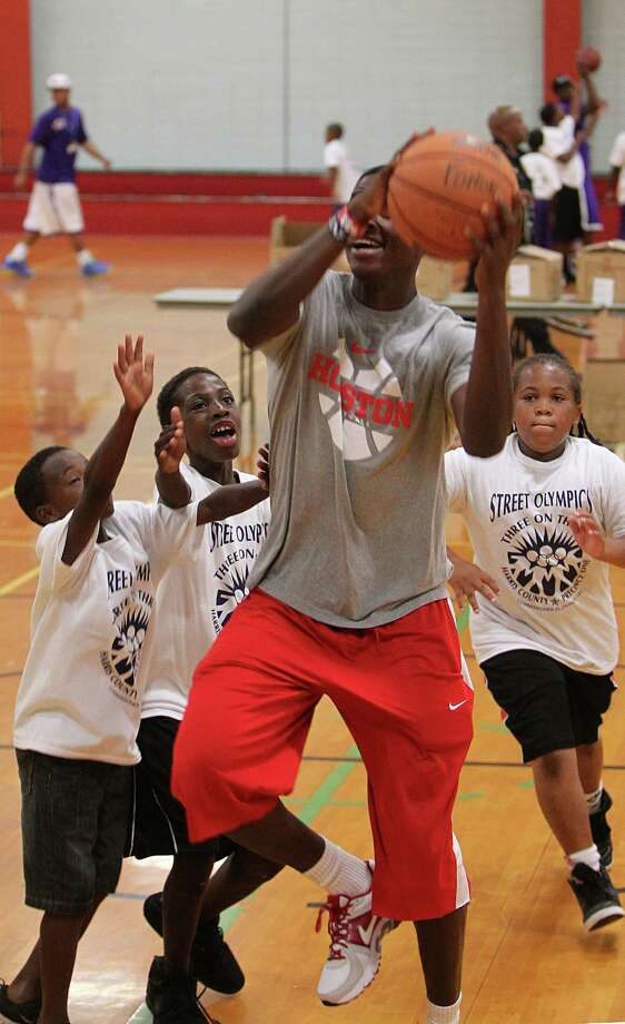 Seth Coles and Joseph Wiley guard University of Houston's basket ball forward Mikhail McLean during a warm up of the Harris County Street Olympics Three On Three Tournament at Fonde Recreation Center on Thursday, July 18, 2013, in Houston. Photo: Mayra Beltran / © 2013 Houston Chronicle
