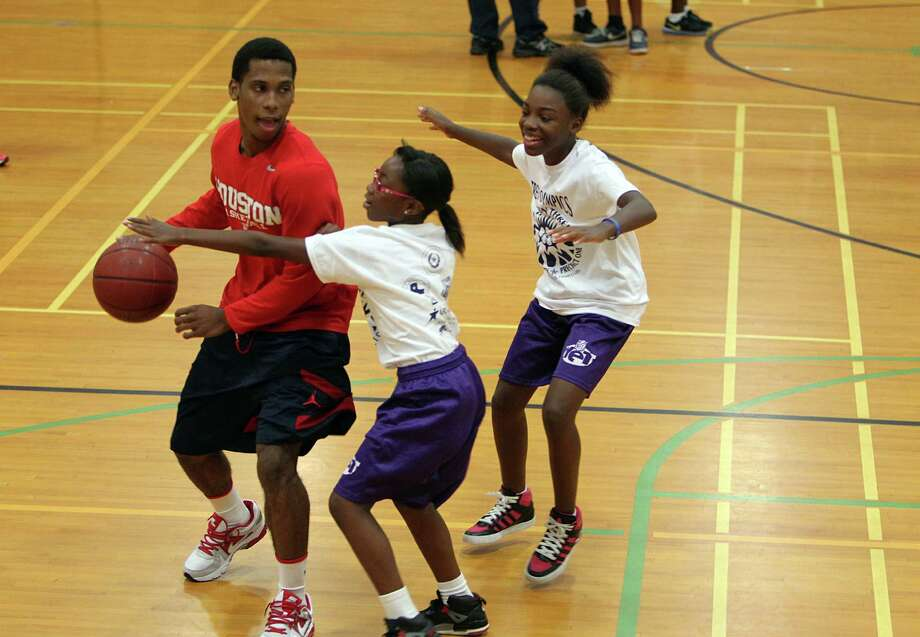 University of Houston's basketball point guard Jimmie Jones play with Raquel Fultz, 10, and Jakyla Cleveland, 11, during a warm up of the Harris County Street Olympics Three On Three Tournament at Fonde Recreation Center on Thursday, July 18, 2013, in Houston. Photo: Mayra Beltran / © 2013 Houston Chronicle