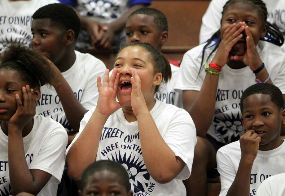 Doris Crisp, 12, joins in the opening games festivities during the start of the Harris County Street Olympics Three On Three Tournament at Fonde Recreation Center on Thursday, July 18, 2013, in Houston. Photo: Mayra Beltran / © 2013 Houston Chronicle
