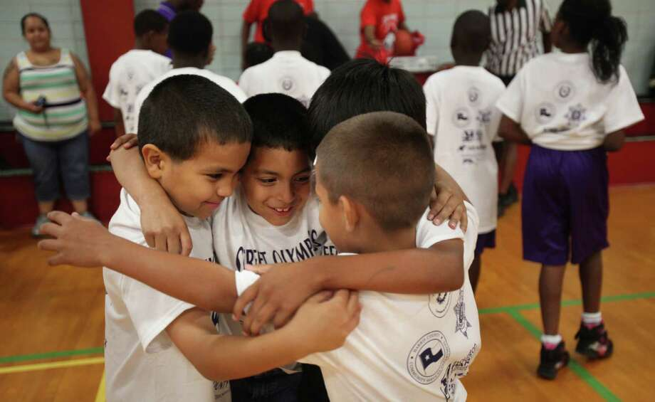 Maximus Messa and Felix Castillo huddle with teammates from Monte Beach Community Center before starting their basketball game during the Three On Three Tournament of the Harris County Street Olympics at Fonde Recreation Center on Thursday, July 18, 2013, in Houston. Photo: Mayra Beltran / © 2013 Houston Chronicle