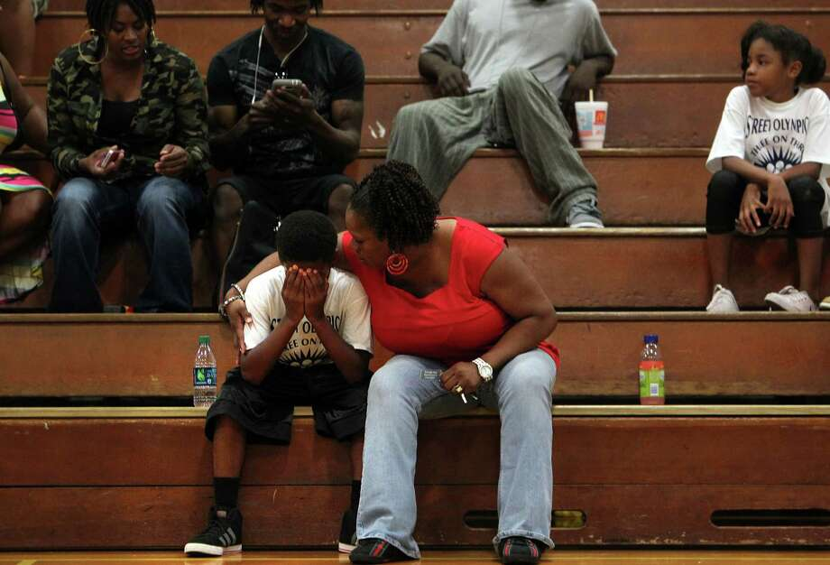 Matthew Golden ,9, reacts to an unfavorable outcome to the basketball game while he is comforted by grandmother Penny Blackshear in the Three On Three Tournament of the Harris County Street Olympics at Fonde Recreation Center on Thursday, July 18, 2013, in Houston. Photo: Mayra Beltran / © 2013 Houston Chronicle