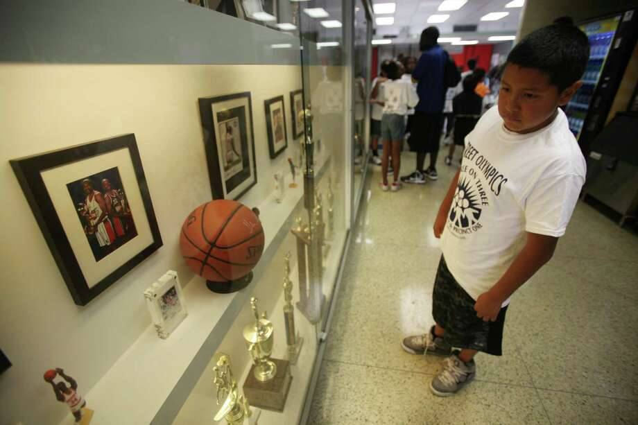 Elias Vidal, 10, views trophies during a break from the Three On Three Tournament of the Harris County Street Olympics at Fonde Recreation Center on Thursday, July 18, 2013, in Houston. Photo: Mayra Beltran / © 2013 Houston Chronicle