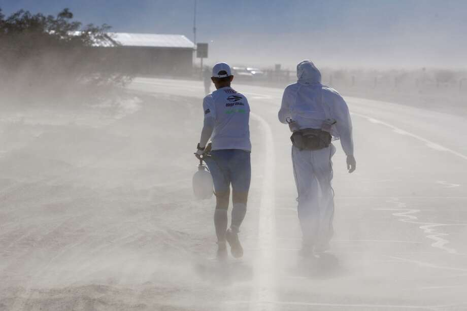 A crew member carrying a water spray bottle and a runner endure blowing dust in strong winds near Stovepipe Wells during the AdventureCORPS Badwater 135 ultra-marathon race on July 15, 2013 in Death Valley National Park, California. Billed as the toughest footrace in the world, the 36th annual Badwater 135 starts at Badwater Basin in Death Valley, 280 feet below sea level, where athletes begin a 135-mile non-stop run over three mountain ranges in extreme mid-summer desert heat to finish at 8,350-foot near Mount Whitney for a total cumulative vertical ascent of 13,000 feet.