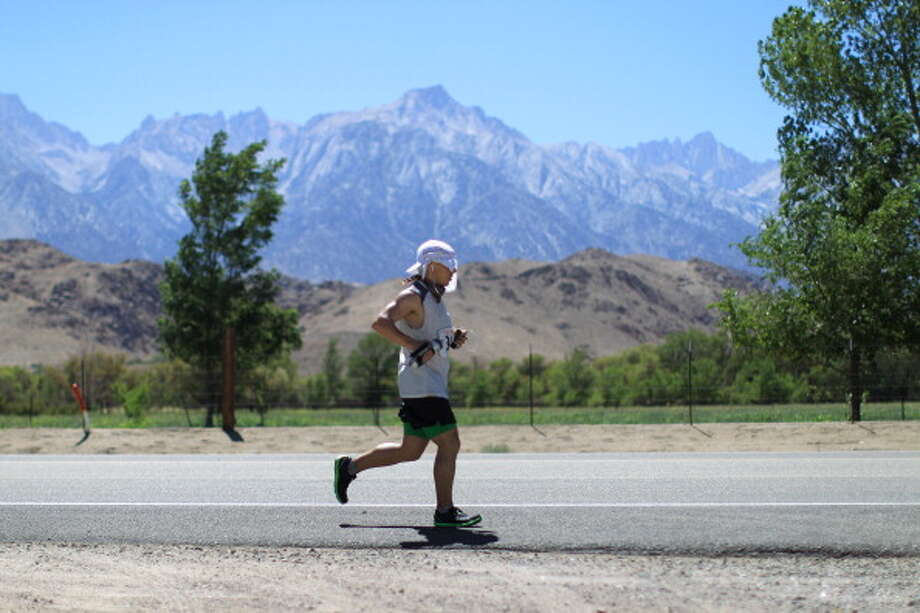 Mount Whitney is seen in the distance (R) as David Ploskonka of Baltimore, Maryland approaches the town of Lone Pine after completing more than 100 miles of the AdventureCORPS Badwater 135 ultra-marathon race on July 16, 2013 outside of Death Valley National Park, California. Photo: David McNew, Getty Images / 2013 Getty Images
