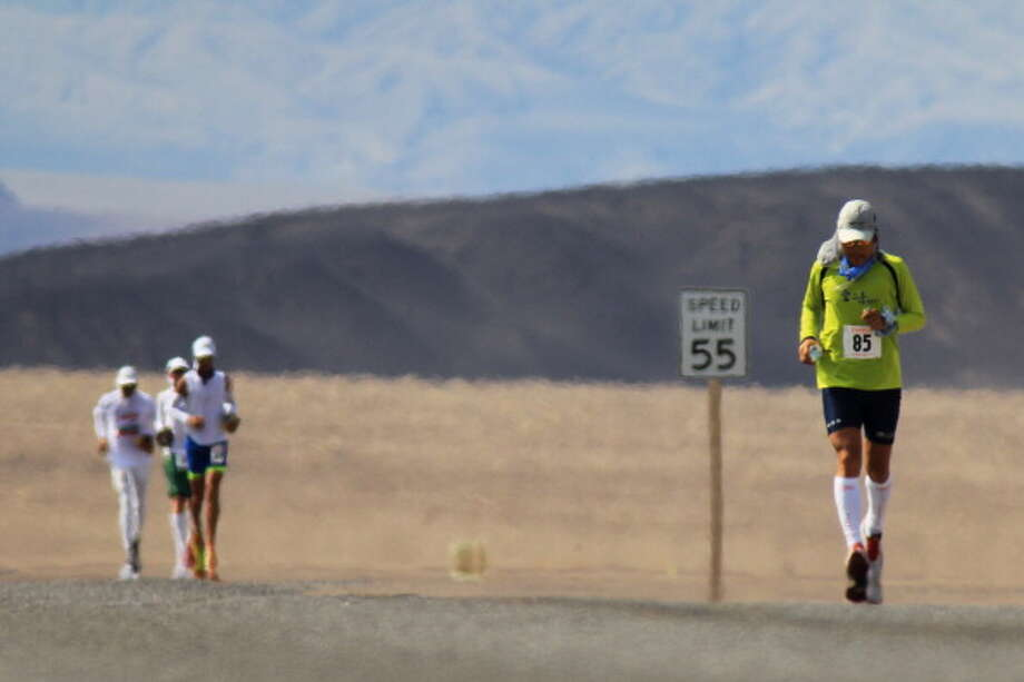 Sukhee Park of South Korea and other runners are seen among heat waves several miles from the start of the AdventureCORPS Badwater 135 ultra-marathon race on July 15, 2013 in Death Valley National Park, California. Photo: David McNew, Getty Images / 2013 Getty Images