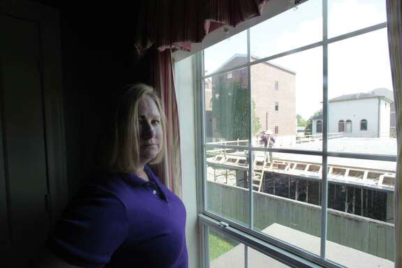 Lauren Lindsay looks out of her daughter's bedroom window where construction on a high-rise continues on Morrison Street in Woodland Heights.