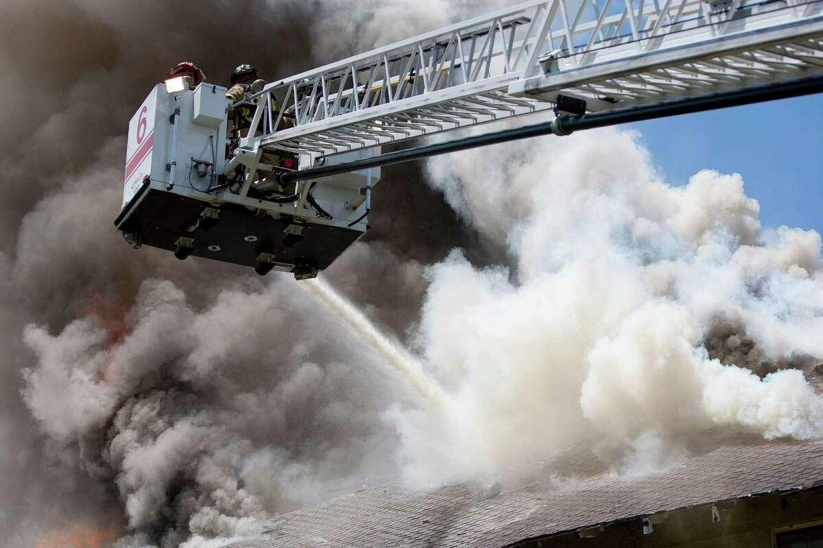 Firefighters respond to a fire of a two-story home that was built in 1915 on Heights Blvd. at 10 1/2 Thursday, July 18, 2013, in Houston. No one was injured in the four-plex home blaze. Owner, Lee Castillo, said he smelt smoke in the attic and saw a very small fire. He called 9-1-1 and