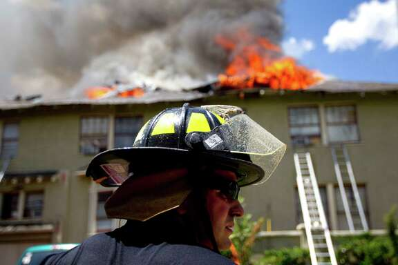 Firefighters respond to a fire of a two-story home that was built in 1915 on Heights Blvd. at 10 1/2 Thursday, July 18, 2013, in Houston.  No one was injured in the four-plex home blaze.