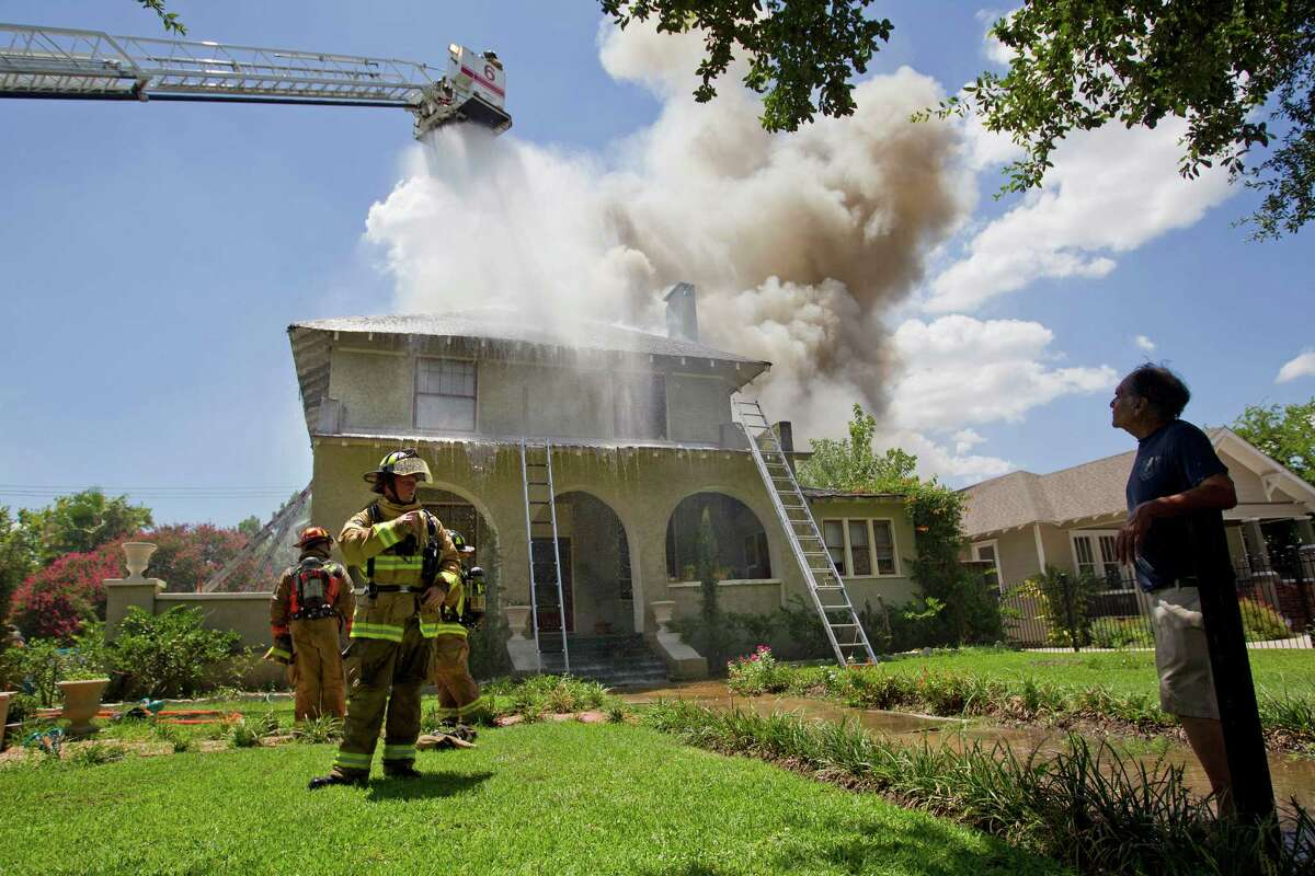 Home owner, Lee Castillo, right, watches as firefighters respond to a fire of a two-story home that was built in 1915 on Heights Blvd. at 10 1/2 Thursday, July 18, 2013, in Houston.
