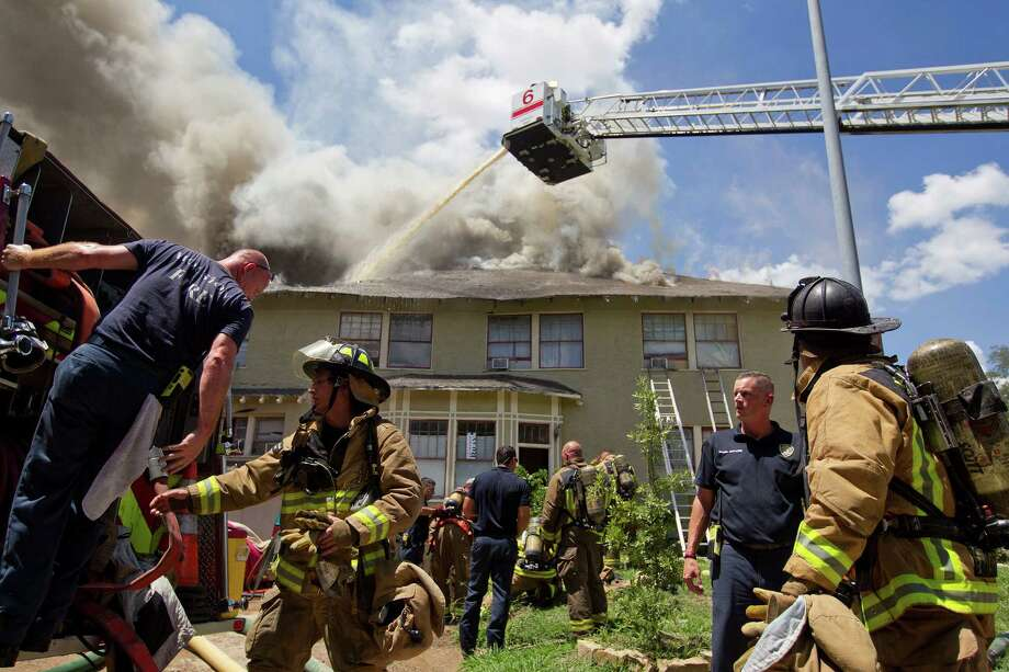 Firefighters respond to a fire of a two-story home that was built in 1915 on Heights Blvd. at 10 1/2 Thursday, July 18, 2013, in Houston. Photo: Johnny Hanson, Houston Chronicle / © 2013  Houston Chronicle