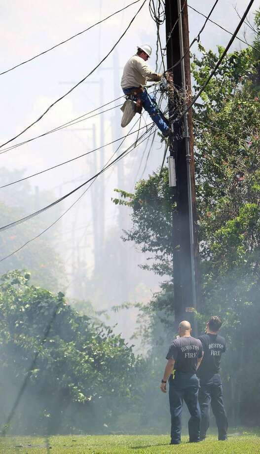 Center Point Energy's Rex Williams cuts the power to a house on fire as Houston firefighters work to knock down the one-alarm fire in the four-plex in the 1000 block of Heights Blvd, Thursday, July 18, 2013, in Houston. Photo: Karen Warren, Houston Chronicle / © 2013 Houston Chronicle