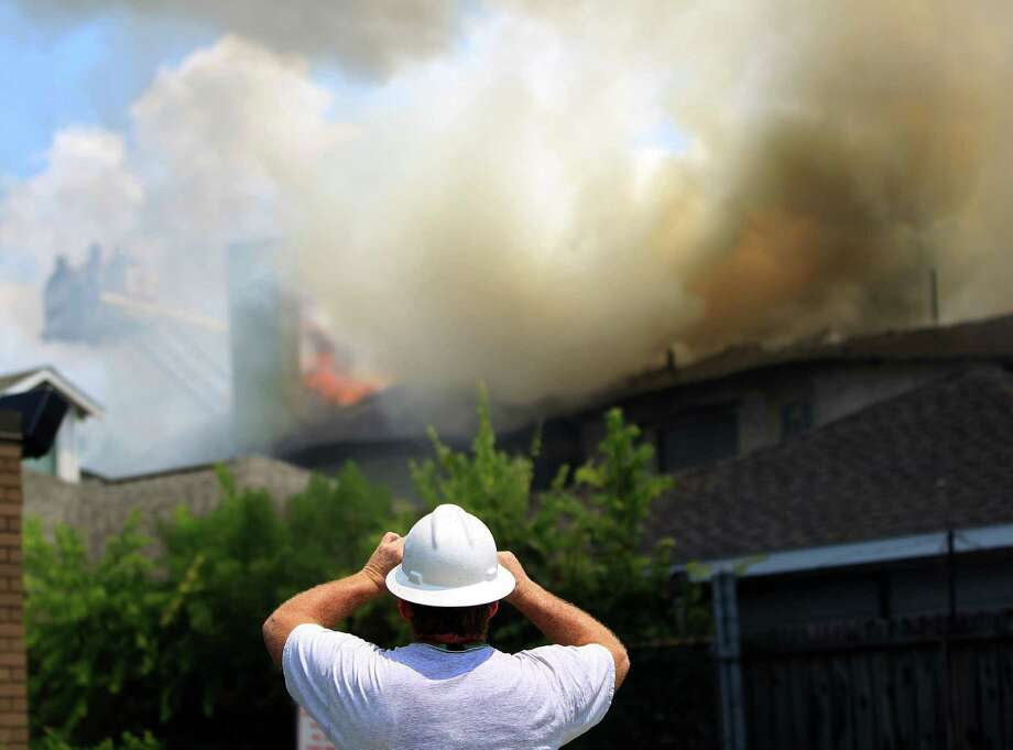 Center Point Energy's Rex Williams takes a photo as Houston firefighters work to knock down the one-alarm fire in the four-plex in the 1000 block of Heights Blvd, Thursday, July 18, 2013, in Houston. Photo: Karen Warren, Houston Chronicle / © 2013 Houston Chronicle