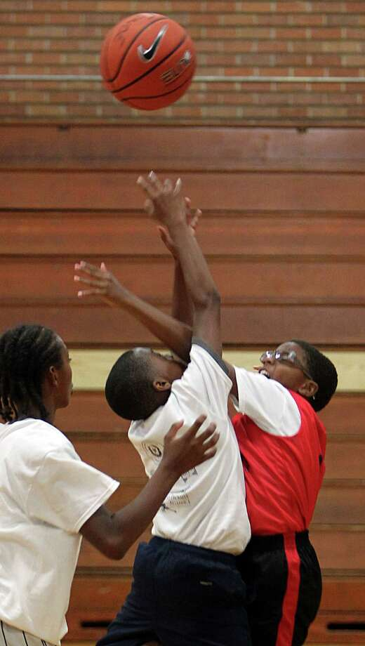 Chaedron Wright tries to pass ball to teammates during a final game of the Three On Three Tournament of the Harris County Street Olympics at Fonde Recreation Center on Thursday, July 18, 2013, in Houston. Photo: Mayra Beltran / © 2013 Houston Chronicle