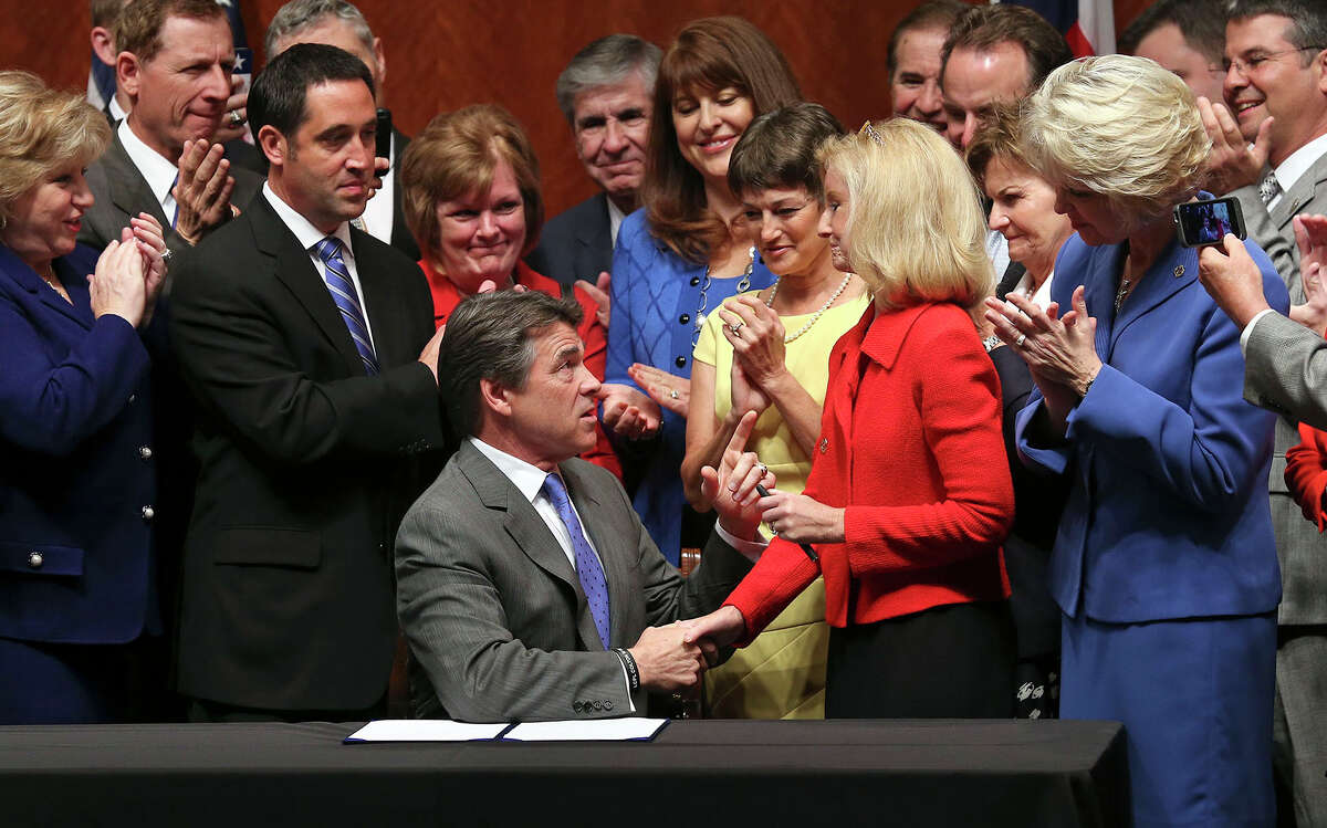 Governor Rick Perry congratulates Representative Jodie Laubenberg R-Parker after he signs into law the abortions restrictions bill on July 18, 2013.