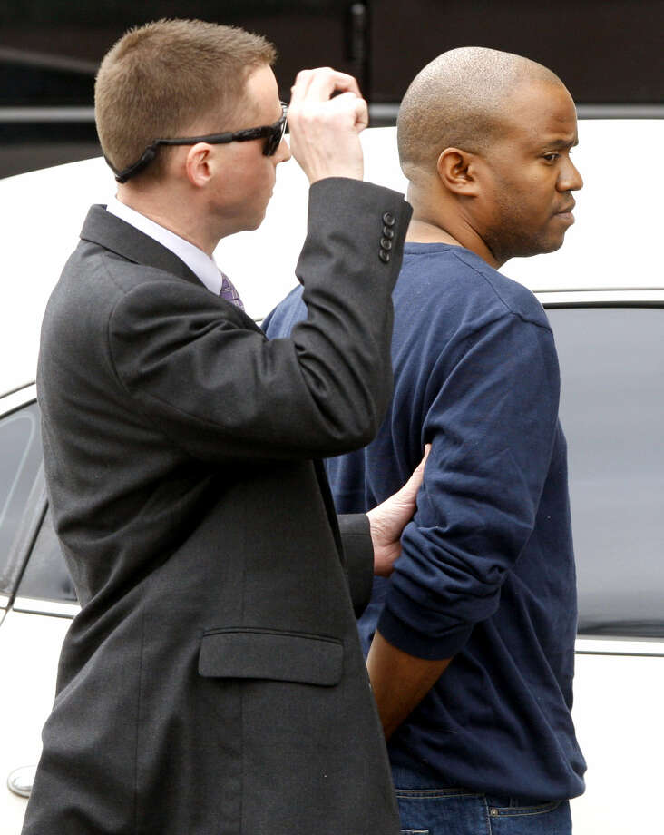 Gemase Lee Simmons (right) is escorted into court by an FBI agent during the legal proceedings against him.