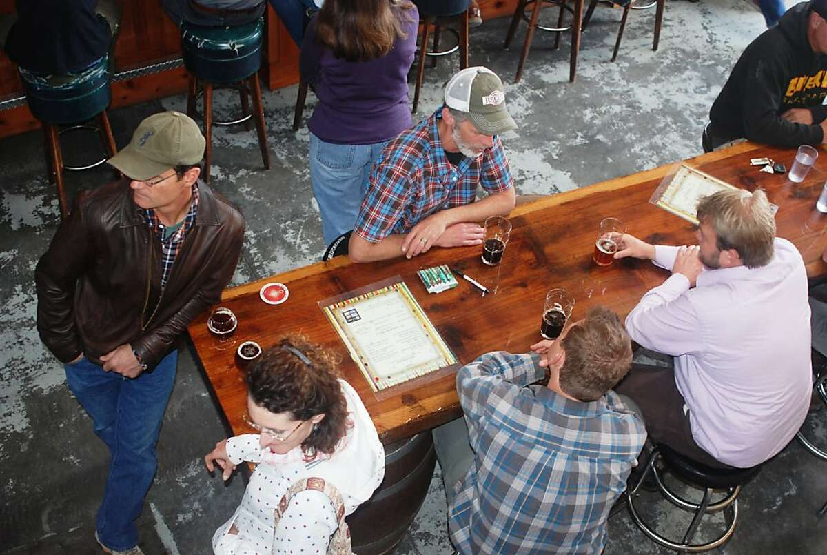 The Redwood Curtain Brewing Cr. in Arcata is located in an old warehouse, with barrels and redwood planks forming the tables.