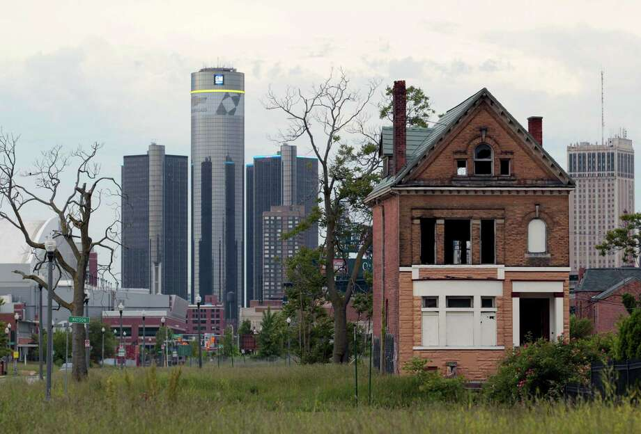 The Renaissance Center, left, the global headquarters of General Motors Co. (GM), stands in downtown Detroit, Michigan. Detroit's filing for bankruptcy on Thursday comes as a painful reminder of the city's rise and fall. Photo: Jeff Kowalsky / © 2013 Bloomberg Finance LP