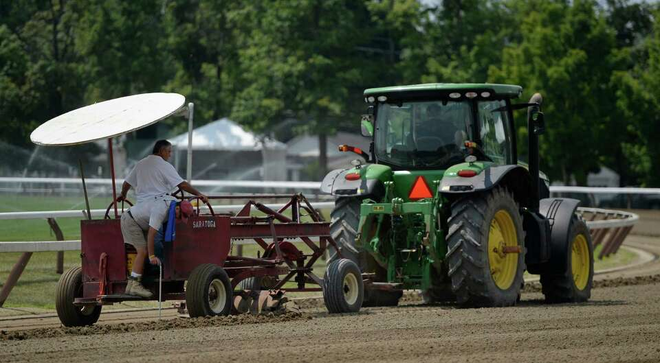 The track crew checks the depth of the main surface in preparation for opening day Thursday, July 18