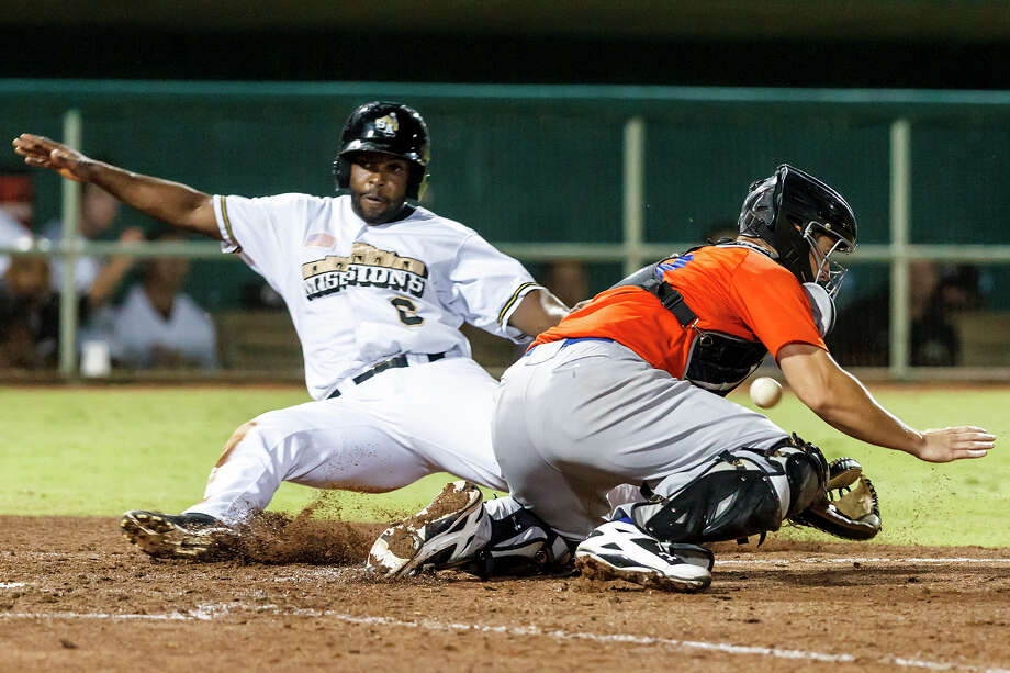 Johan Limonta (left) slides into home to score the only run for the Missions in the bottom of the seventh inning. Despite the loss, the Missions lead the South Division by two games. Photo: Marvin Pfeiffer, San Antonio Express-News / Express-News 2013