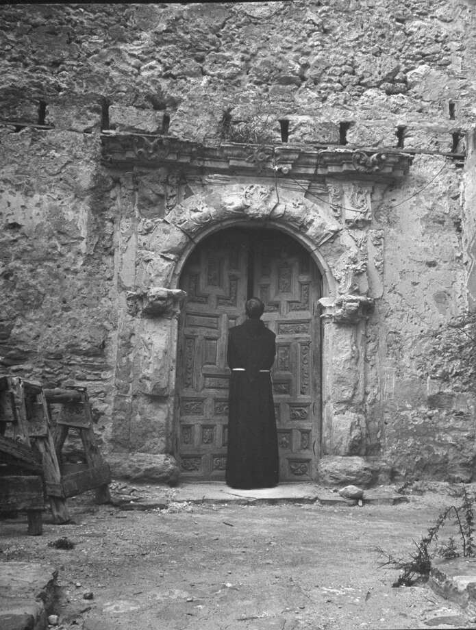 Exterior view of Mission San José, restored, used as church and historic site, showing a monk walking through a stone archway on Oct. 1, 1946. Photo: Cornell Capa, Time & Life Pictures / Getty Images / Time Life Pictures