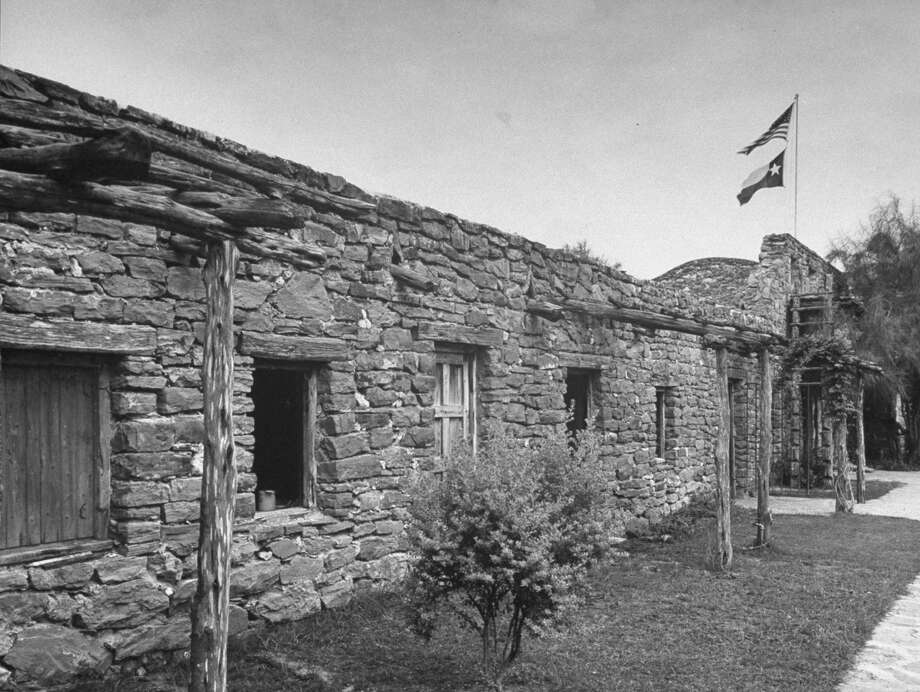 Wall, made of uneven stones around Mission San José, showing flags at entrance on Oct. 1, 1946. Photo: Cornell Capa, Time & Life Pictures / Getty Images / Time Life Pictures