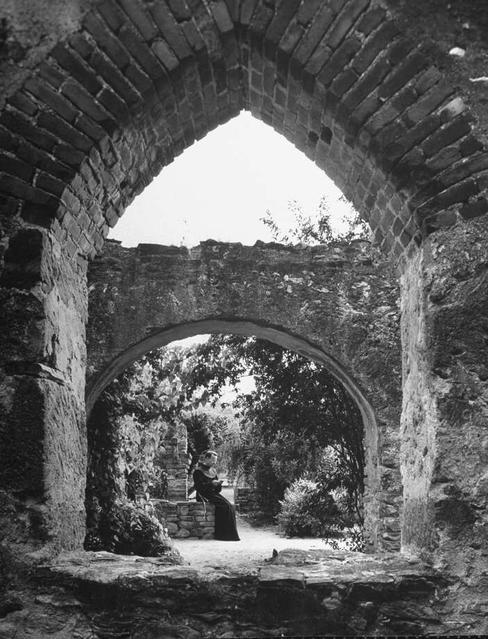 Vine covered walk between enclosing wall and building at Mission San José, supporting arches at intervals, Franciscan monk reading on Oct. 1, 1946. Photo: Cornell Capa, Time & Life Pictures / Getty Images / Time Life Pictures