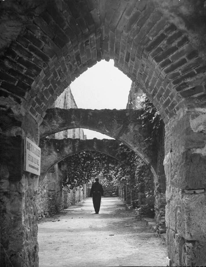 Vine covered walk between enclosing wall and building at Mission San José, supporting arches at intervals, patterns of light on ground, Franciscan monk walking on Oct. 1, 1946. Photo: Cornell Capa, Time & Life Pictures / Getty Images / Time Life Pictures