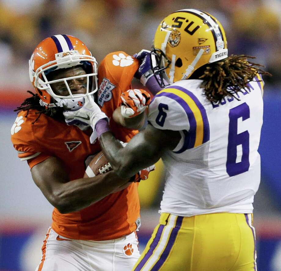 A former Houston high school player - LSU safety Craig Loston of Eisenhower - clashes with a future Houston professional player - Clemson wide receiver DeAndre Hopkins, the top pick of the Texans. Photo: David Goldman, STF / AP