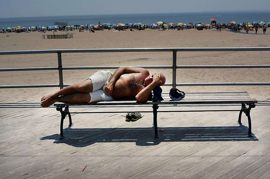 NEW YORK, NY - JULY 18: A man rests along the the Coney Island boardwalk on one of the hottest weeks in recent New York City history on July 18, 2013 in New York City. With daily temperatures in the high 90's and with the heat index making it feel in the triple digits, many New Yorkers are doing what they can to stay cool. A break from the heatwave is not expected until Saturday evening at the earliest.  (Photo by Spencer Platt/Getty Images) Photo: Spencer Platt, Getty Images