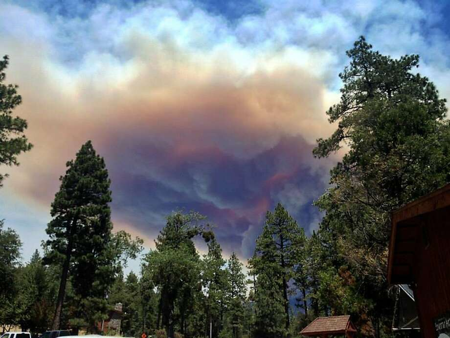 This July 17, 2013 image provided by Meagan Greene shows wildfire smoke near Idyllwild, Calif. The blaze about 100 miles east of Los Angeles had grown to more than 35 square miles in size and had destroyed at least six houses and mobile homes. Tensions heightened late Wednesday after winds shifted, causing the fire to change course and head in the direction of Idyllwild, an artist community and hiking destination in the San Jacinto Mountains.(AP Photo/Meagan Greene) Photo: Meagan Greene, Associated Press