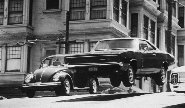 A car flies through the air while traveling down a San Francisco street in a still from the film, 'Bullitt,' directed by Peter Yates, 1968.